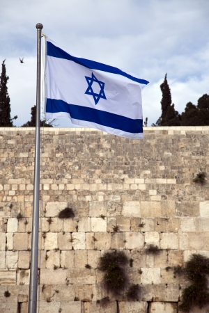 Israel flag fluttering in the wind in front of the holy Wailing Wall, one of the most sacred places to the Jewish people. photo