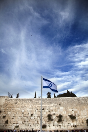 jewish prayer: Israel flag fluttering in the wind in front of the holy Wailing Wall, one of the most sacred places to the Jewish people. Stock Photo