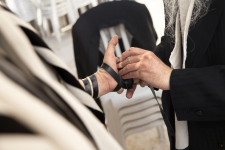 The hand of an adult Caucasian man is being wrapped in a leather strap, part of the Jewish phylacteries (Teffilin, Tefilin, Tfilin) wearing ceremony and prayer.