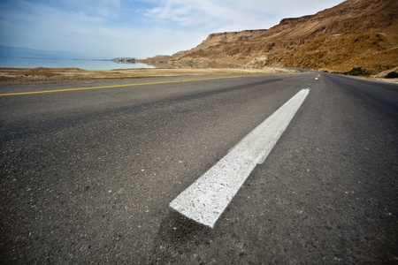 extreme angle: An empty road in the desert, shot with a low and very wide angle. The Sodom mountains are seen in the horizon, and the Dead sea is just to the left of the frame.