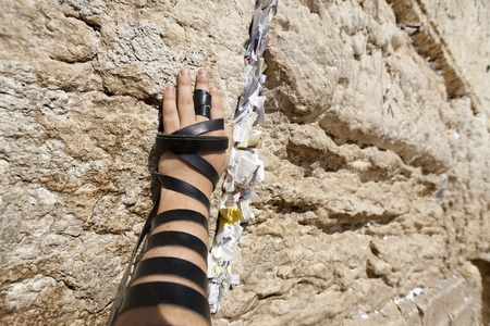 The left hand of a Jewish adult (early 30s) Caucasian man wrapped with Phylacteries, resting on the holy Western Wall (aka Wailing Wall) in the old city of Jerusalem, Israel.