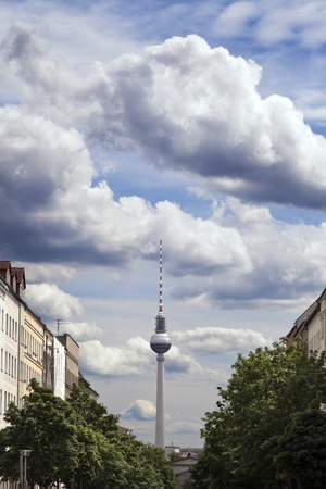 View of the blocks of buildings that stretch along Strelitzer strasse and the Berlin Television Tower  Fernsehturm  in the distance, beneath blue cloudy sky