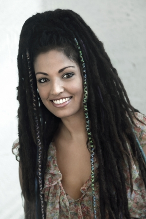 optimisim: A good looking woman in her late 20s with long dark dreadlocks, looking and smiling to the camera. Stock Photo
