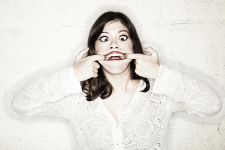 exaggerate: Portrait of a beautiful young woman making a monster face. Her big eyes wide open and cross eyed, looking in sheer terror; her hands opening her mouth as wide as possible. Total look is very goofy. Not so frightening after all.