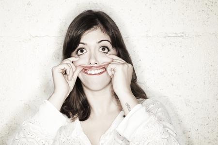 occhi sbarrati: Ritratto di una bella giovane donna fare un maniaco  mostro faccia goofy. I suoi grandi occhi spalancati, mentre le sue mani si sono tese bocca upware Archivio Fotografico