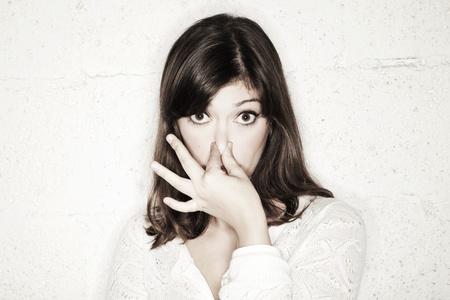 persona confundida: Retrato de una joven y bella mujer mirando a la cámara con los ojos bien abiertos y tapándose la nariz con dos dedos. Al parecer, algo huele mal. Foto de archivo
