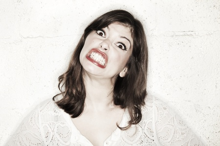 Portrait of a beautiful young woman looking at the camera with an exaggerated angry expression, clutching her teeth together, trying to be frightening.