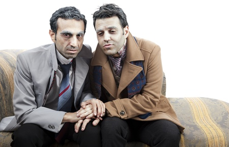 pitiful: Two adult man (mid 30s and mid 20s) wearing old-man clothes and makeup, sitting on a used up vintage sofa. They both have quite a miserable and pitiful appearance. Isolated on white background.