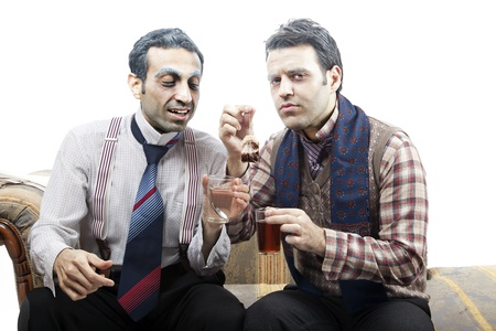 Two adult man (mid 30s and mid 20s) wearing old-man clothes and makeup, sitting on a used up vintage sofa. They seems to be sharing a teabag, moving it from one glass to the other. Isolated on white background. photo