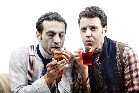 pitiful: Two adult man (mid 30s and mid 20s) wearing old-man clothes and makeup, sitting on a used up vintage sofa. Looking rather cold and pitiful they are both warming themselves with a glass of hot tea. Isolated on white background. Stock Photo