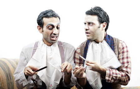 conversating: Two adult man (mid 30s and mid 20s) wearing old-man clothes and makeup, sitting on a used up vintage sofa. They both wear napkins on their necks and holding cuttlery, suggesting they are having a meal. They seem to be in the middle of a vivid conversati
