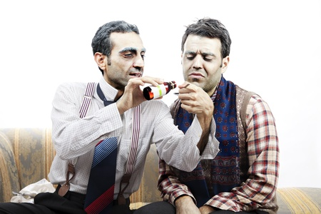 reluctant: Two adult man (mid 30s and mid 20s) wearing old-man clothes and makeup, sitting on a used up vintage sofa. The left one is just about to pour some syrup onto a teaspoon, and the extremely reluctant expression of his friend indicates he is supposed to dr Stock Photo