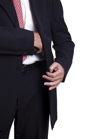 An adult wearing a suit pulling a 9mm gun out of its holster beneath the jacket. Isolated on white background.