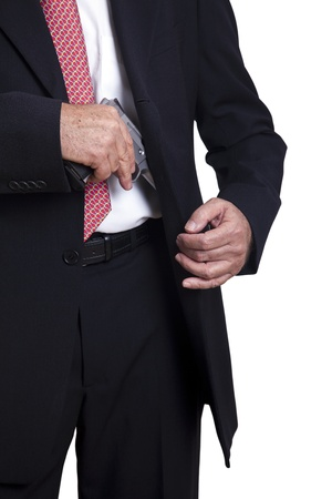 concealed: An adult wearing a suit pulling a 9mm gun out of its holster beneath the jacket. Isolated on white background.