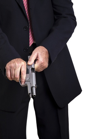 A mature adult man wearing a suit, cocking a 9mm gun and getting ready to use it. Isolated on white background. Stock Photo