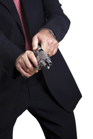 A mature adult man wearing a suit, cocking a 9mm gun and getting ready to use it. Isolated on white background. photo