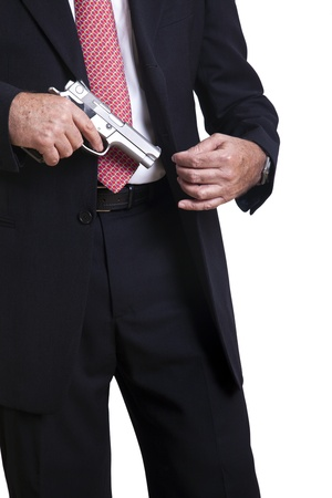 concealed: A mature adult man wearing a suit, pulling a 9mm gun out of its holster beneath the jacket. Isolated on white background. Stock Photo