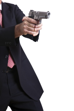 concealed: A mature adult man wearing a suit, holding a 9mm gun with both hands aiming it to the target. Isolated on white background.