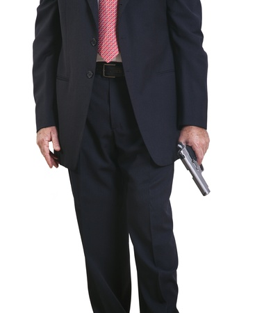 Part of a mature adult man wearing a suit and tie, standing with a gun in his left hand. Isolated on white background. Banco de Imagens