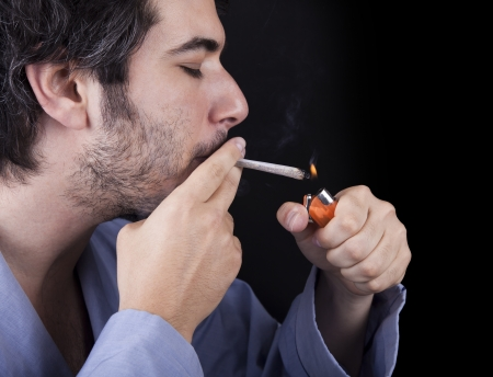 reefer: Closeup of an adult man (30 years old) with his profile to the camera. He appears to be quite a bum, being unshaved and wearing a light blue fabric robe, concentrated in lighting a marijuana jspliff (aka reefer; joint) with a simple disposable half-transp