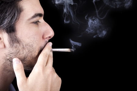 Closeup of an adult man (30 years old) with his profile to the camera. He appears to be quite a bum, being unshaved and wearing a light blue fabric robe, concentrated in smoking a marijuana spliff (aka reefer; joint). Isolated on black background.