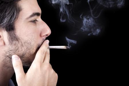 hombre fumando: Primer plano de un hombre adulto (30 años) con el perfil a la cámara. Él parece ser un vago, siendo sin afeitar y vestido con una túnica de tela de color azul claro, concentrada en fumar un porro de marihuana (también conocido como reefer, articulaciones). Aislado sobre fondo negro.