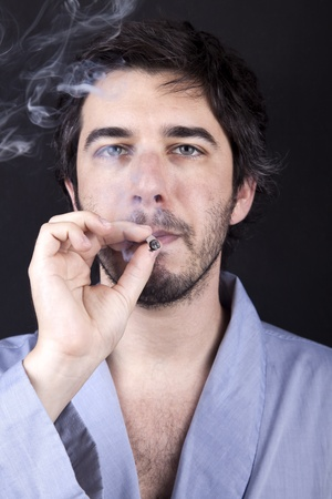 Medium closeup of an adult man (30 years old), which  appears to be quite a bum, being unshaved and wearing a light blue fabric robe, numbingly gazing forward, concentrated in smoking a marijuana spliff (aka reefer; joint). Dark gray background. Stock Photo - 19281643