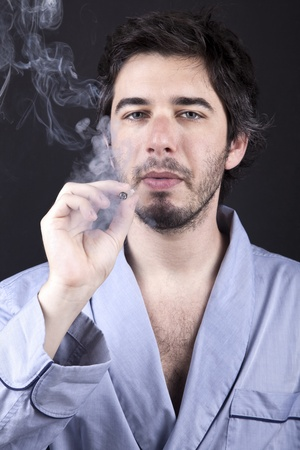 medium closeup: Medium closeup of an adult man (30 years old), which  appears to be quite a bum, being unshaved and wearing a light blue fabric robe, numbingly gazing at the camera, concentrated in smoking a marijuana spliff (aka reefer; joint). Dark gray background.