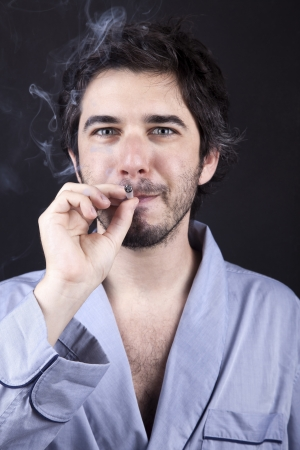 Medium closeup of an adult man (30 years old), which  appears to be quite a bum, being unshaved and wearing a light blue fabric robe, staring at the camera with a satisfied look while smoking a marijuana spliff (aka reefer; joint). Dark gray background. Stock Photo - 19281645