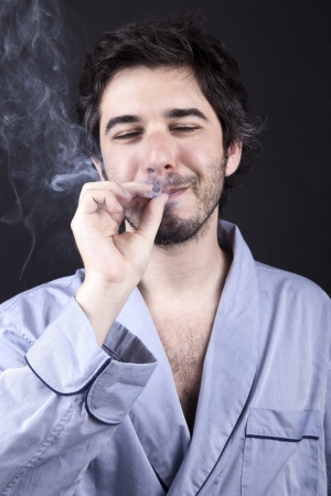 medium closeup: Medium closeup of an adult man (30 years old), which  appears to be quite a bum, being unshaved and wearing a light blue fabric robe, closing his eyes with a delighted expression while smoking a marijuana spliff (aka reefer; joint). Dark gray background.