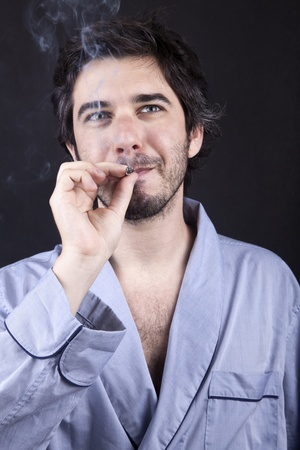 medium closeup: Medium closeup of an adult man (30 years old), which  appears to be quite a bum, being unshaved and wearing a light blue fabric robe, looking upwith a satisfied look while smoking a marijuana spliff (aka reefer; joint). Dark gray background.
