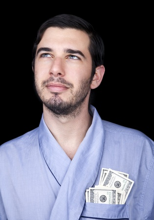 medium closeup: Medium closeup of an adult man (30 years old). Although his hair is neatly combed, he appears to be quite a bum, being unshaved and wearing a light blue fabric robe. In the robes front pocket there are numerous 100 US Dollar bills, which indicate hes a