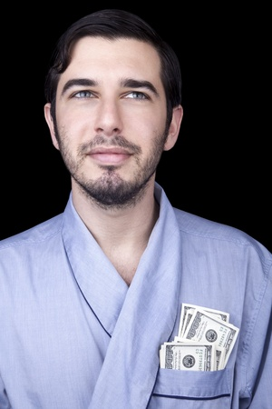 Medium closeup of an adult man (30 years old). Although his hair is neatly combed, he appears to be quite a bum, being unshaved and wearing a light blue fabric robe. In the robes front pocket there are numerous 100 US Dollar bills, which indicate hes a  photo