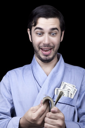 medium closeup: Medium closeup of an adult man (30 years old). Although his hair is neatly combed, he appears to be quite a bum, being unshaved and wearing a light blue fabric robe. Hes looking down with an insanely pleased expression at a stack of 100 US$ bills that he