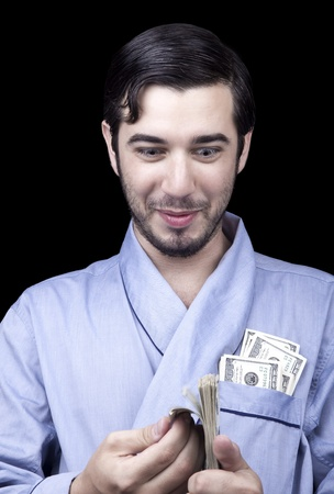 combed: Medium closeup of an adult man (30 years old). Although his hair is neatly combed, he appears to be quite a bum, being unshaved and wearing a light blue fabric robe. Hes looking down with an insanely pleased expression at a stack of 100 US$ bills that he