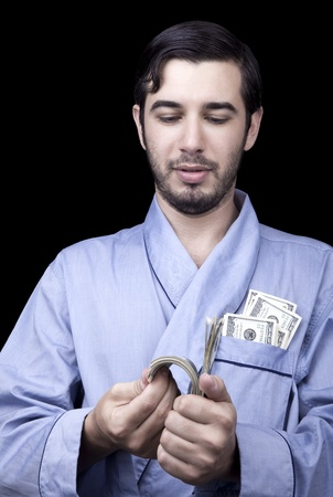 Medium closeup of an adult man (30 years old). Although his hair is neatly combed, he appears to be quite a bum, being unshaved and wearing a light blue fabric robe. Hes looking down with quite a satisfied expression at a stack of 100 US$ bills that hes photo