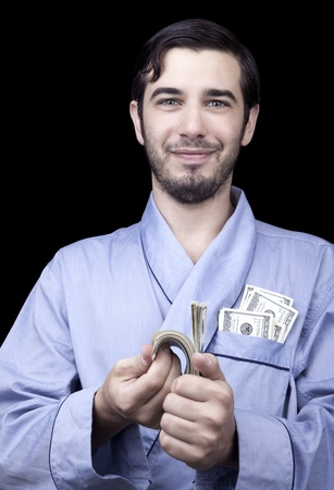 combed: Medium closeup of an adult man (30 years old). Although his hair is neatly combed, he appears to be quite a bum, being unshaved and wearing a light blue fabric robe. Hes looking at the camera with quite a satisfied expression at a stack of 100 US$ bills