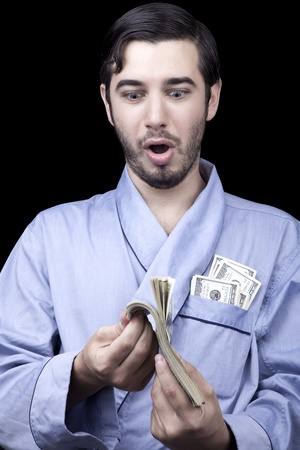 combed: Medium closeup of an adult man (30 years old). Although his hair is neatly combed, he appears to be quite a bum, being unshaved and wearing a light blue fabric robe. Hes looking down with an awed & surprised expression at a stack of 100 US$ bills that he Stock Photo