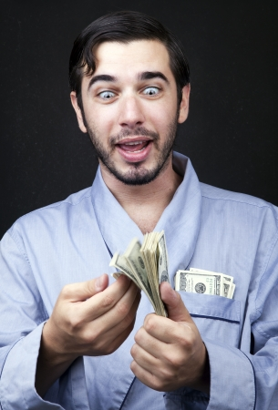 Medium closeup of an adult man (30 years old). Although his hair is neatly combed, he appears to be quite a bum, being unshaved and wearing a light blue fabric robe. He's looking down with an insanely pleased expression at a stack of 100 US$ bills that he photo