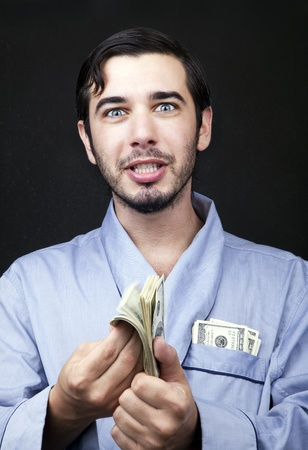 Medium closeup of an adult man (30 years old). Although his hair is neatly combed, he appears to be quite a bum, being unshaved and wearing a light blue fabric robe. He's looking at the camera with an insanely pleased expression, probably because of the s photo