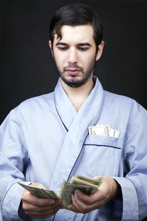 medium shot: Medium shot of an adult man (30 years old). Although his hair is neatly combed, he appears to be quite a bum, being unshaved and wearing a light blue fabric robe. Hes looking down with a serious expression, counting the stack of 100 US$ bills in his hand