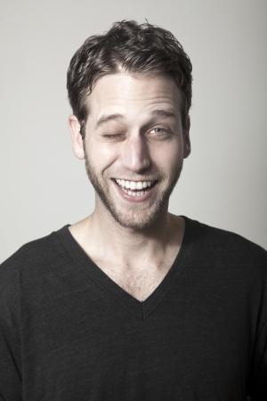 clin d oeil: Studio portrait d'un homme adulte de race blanche dans son d�but des ann�es 30 sur fond gris. Il semble �tre dans une bonne humeur, un clin d'?il b�tement � la cam�ra avec un grand sourire plein de dents sur son visage.