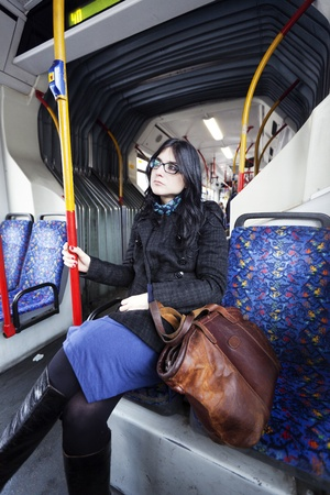 early 30s: Caucasian adult woman in her early 30s sitting in a rather empty articulated bus, gazing into space waiting for her stop. Her clothing suggests its winter time. Stock Photo