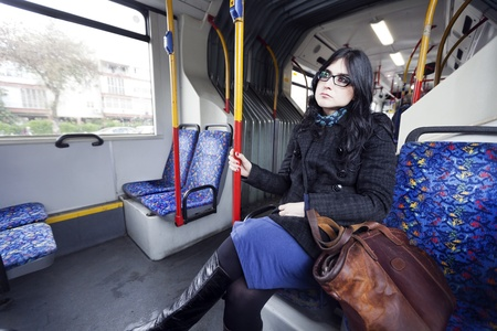 suggests: Caucasian adult woman in her early 30s sitting in a rather empty articulated bus, gazing into space waiting for her stop. Her clothing suggests its winter time. Stock Photo