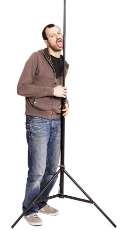 early 30s: An adult caucasian man at his early 30s wearing casual sneakers, a pair of blue jeans and a hoodie over a black t-shirt. He is making a passionate licking gesture on the stands extended pole while looking at the camera with bedroom eyes. Isolated on whi