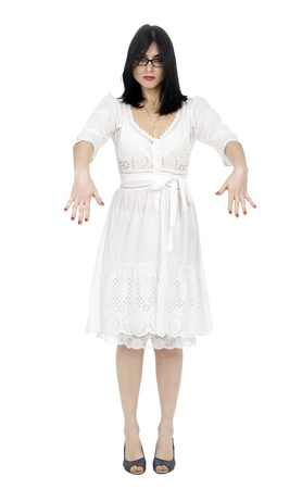 emotionless: An adult (early 30s) black haired caucasian woman, wearing a lovely white summer dress which stands in complete contradiction to her intimidating emotionless facial expression, and zombie-like positioning of her arms. Sadly, it appears she is turning int Stock Photo