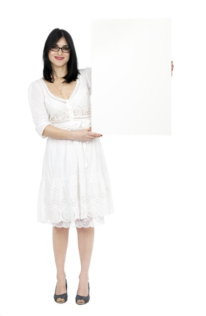 early 30s: An adult (early 30s) black haired caucasian woman, wearing a lovely white summer dress and holding a blank sign next to her while giving the camera a toothy smile. Isolated on white background.