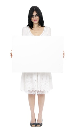 early 30s: An adult (early 30s) black haired caucasian woman, wearing a lovely white summer dress and holding a blank sign in her front while giving the camera a toothy smile. Isolated on white background.