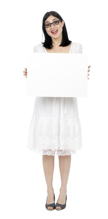early 30s: An adult (early 30s) black haired caucasian woman, wearing a lovely white summer dress and holding a blank sign in her front while giving the camera what seems to be a loud cheer (Surprise!!!). Isolated on white background.