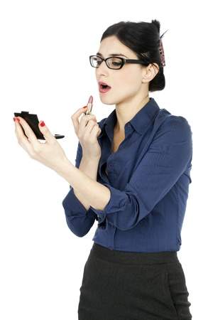 early 30s: An adult (early 30s) black haired caucasian woman wearing a blue buttoned shirt and a dark gray skirt,looking at a small makeup mirror shes holding in her hand, and about to renew her lipstick. Isolated on white background.